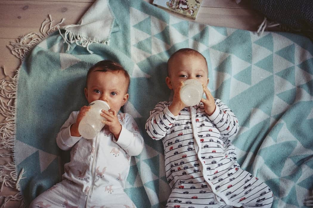 Two toddlers feeding from milk bottles
